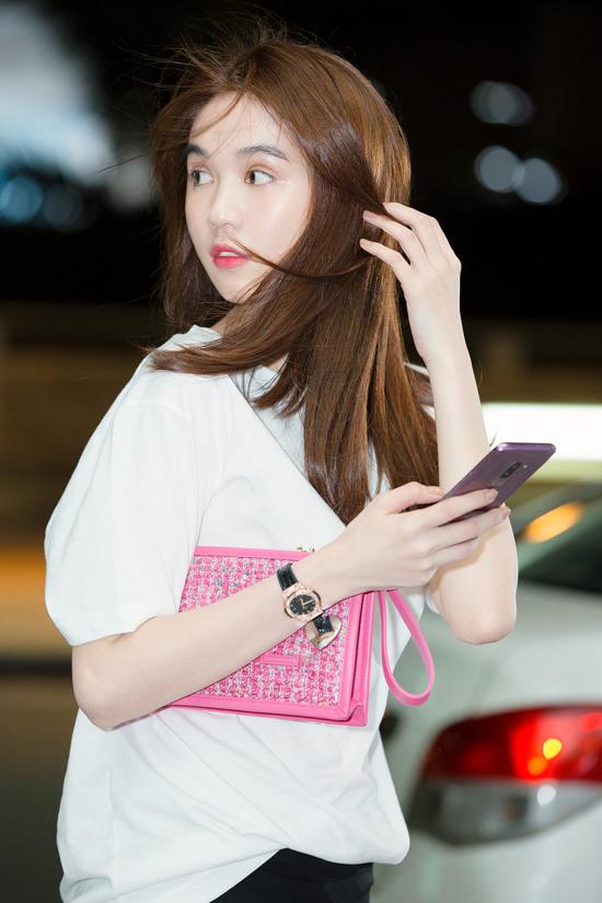 Khi ra sân bay với phong cách đơn giản, trẻ trung, Ngọc Trinh vẫn tạo điểm nhấn nhẹ nhàng cho tổng thể bằng mẫu cltuch vải twed hồng của Chanel.