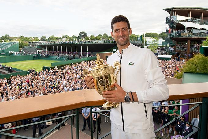 Djokovic chụp ảnh cùng chiếc Cup vô địch Wimbledon 2019 trong sự chúc mừng của các fan. Ảnh: AELTC.