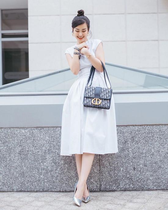 Đơn giản, thanh lịch nhưng không kém phần sang chảnh là bộ váy cổ điển của Đông Nhi. Khi sử dụng trang phục đơn sắc, ca sĩ tạo điểm nhấn bằng phụ kiện túi Dior hợp xu hướng mới.