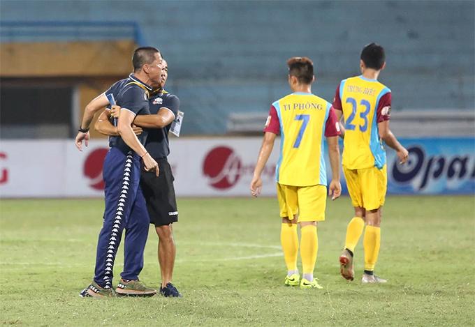 Trợ lý ngăn HLV Chu Đình Nghiêm khi vào sân phản ứng trọng tài sau trận đấu với Khánh Hòa. Ảnh: Đương Phạm.