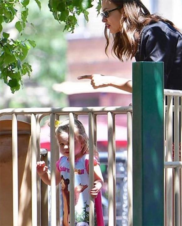 Hai mẹ con vui đùa trong công viên nhỏ.