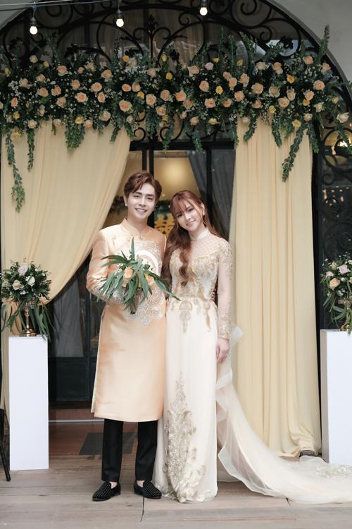 Trong dịp hỷ sự, Thu Thủy và chồng đều diện áo dài đôi mang tông vàng đồng. Chiếc áo của cô dâu là áo dài cách tân mang phom dáng váy cưới với đuôi xòe rộng.