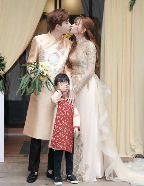 Chú rể say đắm khóa môi cô dâu trong khi cậu con trai riêng của Thu Thủy ngượng ngùngche mặt lại.