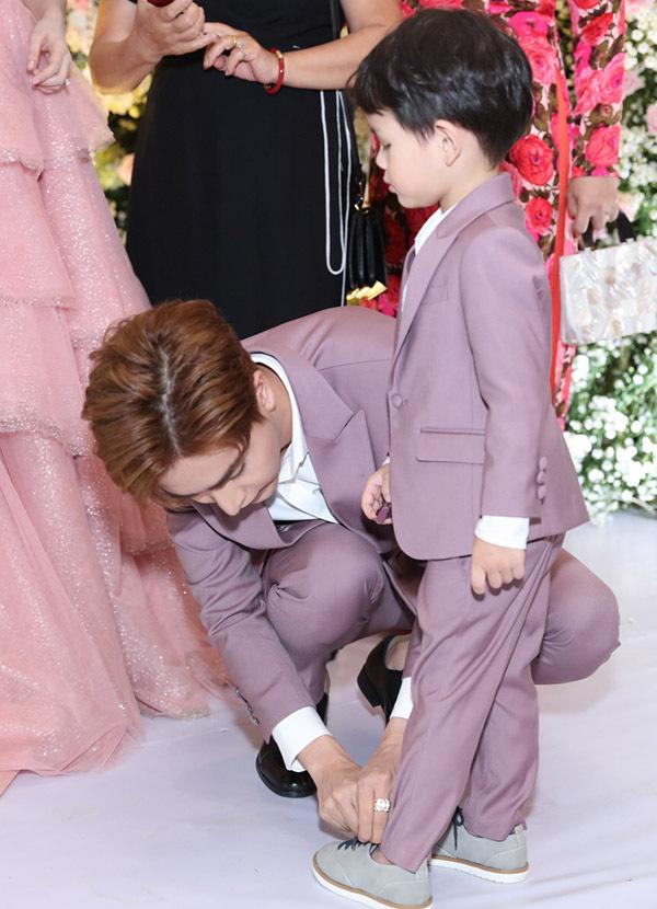 Doanh nhân 9X ân cần chăm sóc, chỉnh trang phục cho con riêng của vợ. Anh chưa từng làm cha nhưng rất khéo dỗ dành trẻ nhỏ.