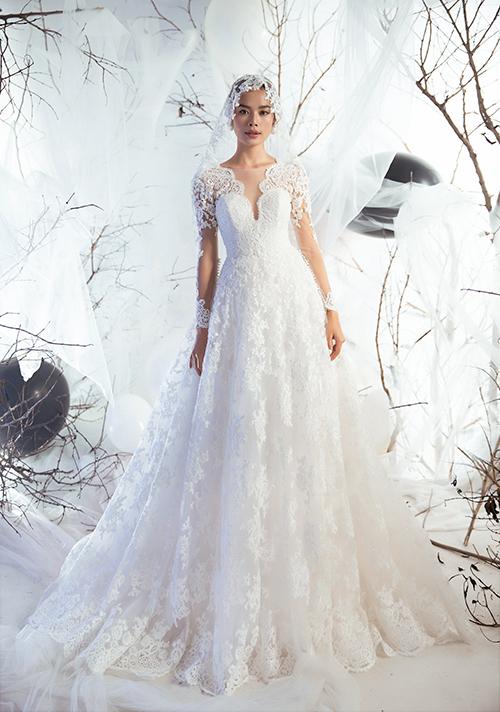 Váy cổ chữ V khoét ngực sâu trên nền ren Pháp sang trọng được kết hợp với lúp cưới từ voan cùng họa tiết giúp diện mạo của nàng trở nên nổi bật.