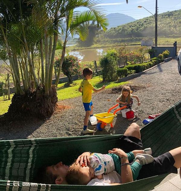 Felipe Luis ôm bé nhỏ ngủ trên võng trong khi hai bé lớn chơi bên cạnh trong biệt thự.