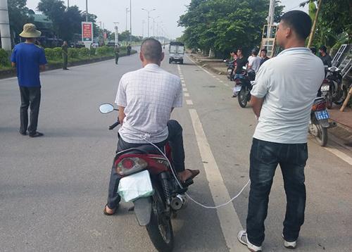 Toán thực nghiệm lại cảnh ngồi trên xe máy nhìn đồng bọn bắt cóc thiếu nữ giao gà. Ảnh:Thu Trang.