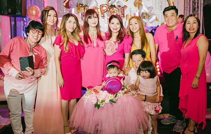 Diễn viên Hiền Mai (thứ tư từ trái qua), đạo diễn Trần Vi Mỹ (thứ hai từ phải qua) và nhiều bạn bè của Thanh Thảo mặc trang phục gam hồng, mừng thôi nôi bé Talia.