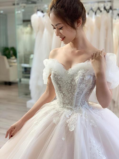 Năm nay, chiếc váy cưới Cinderella với phần vai trễviền bằng những lớp voan mỏng, tạo dáng như các cánh hoa nở, đan xen nhau rất được lòng các nàng dâu. Thân trên của váy được dựng theo kỹ thuật corset gồm 11 thanh nẹp thân trong suốt, giúp định hình vòng hai nhỏ nhắn và đẩy khuôn ngực vào dáng giọt lệ căng tròn.