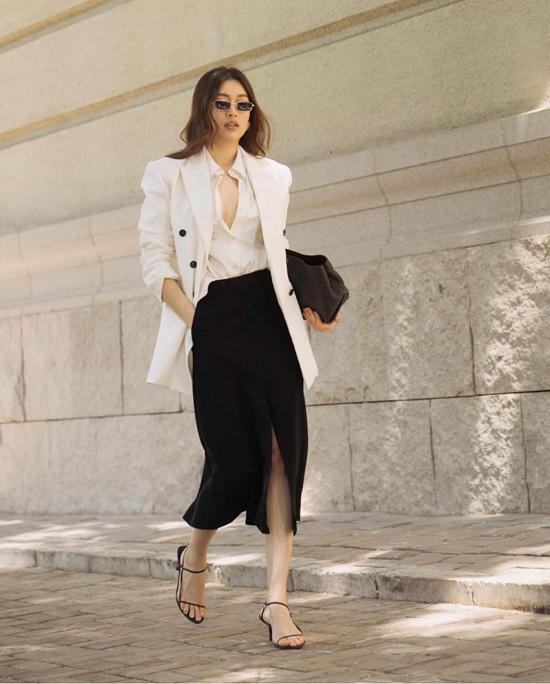 Set đồ trắng đen kết hợp một cách nhịp nhàng giữa áo vest dáng rộng, sơ mi, chân váy xẻ và các phụ kiện tiệp màu.