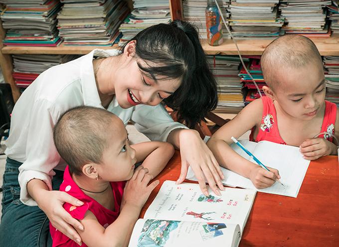 Người đẹp Kiều Loan hướng dẫn các em nhỏ viết chữ.