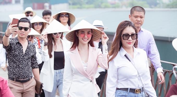 Cô đội nón lá để che nắng, cùng dàn người đẹp và NTK Nhật Dũng, cựu người mẫu Thúy Hằng, diễn viên Công Dũng đi bộ qua cầu.
