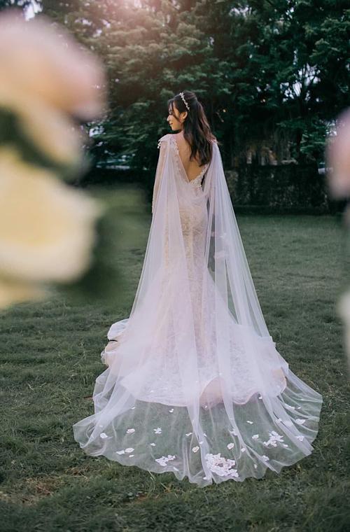 Chiếc áo choàng rời phía sau tạo nét thướt tha theo từng bước đi uyển chuyển của cô dâu.