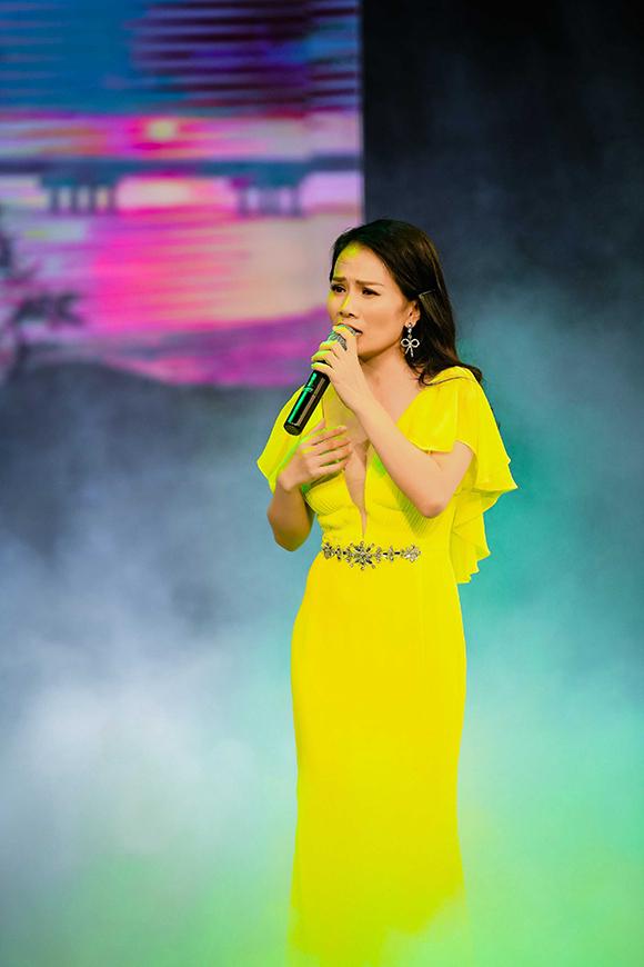 Đinh Thành Lê khoe vẻ gợi cảm qua bộ váy xẻ sâu trên sân khấu. Cô hát Gửi sông La và Hà Tĩnh mình thương.