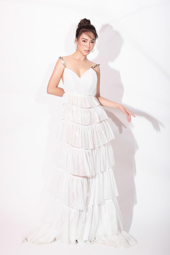 Váy xẻ cổ chữ V xếp tầng mang đến vẻ ngọt ngào, trẻ trung nhưng vẫn quyến rũ. Hai dây áo được đính kết từ kim loại và đá lấp lánh khiến trang phục thêm điệu đà.