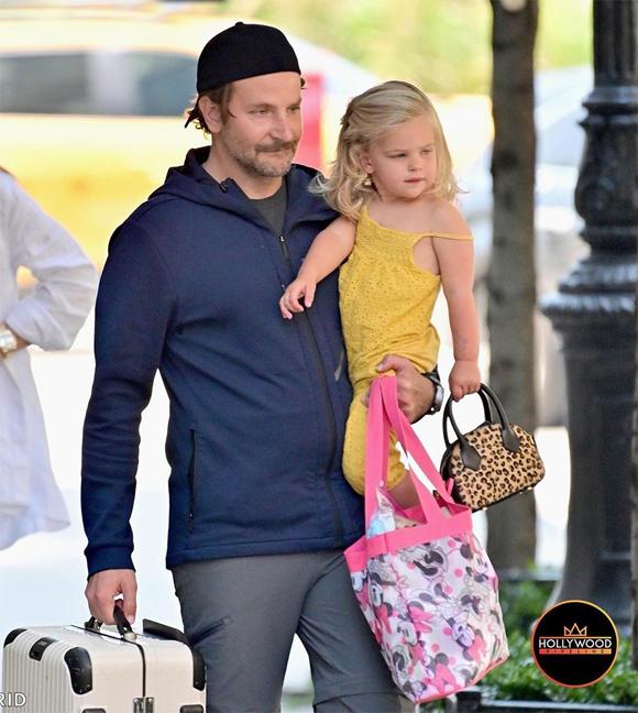 Nam diễn viên mang theo vali và túi Mickey Mouse đựng đồ cho con gái trong khi bé Lea xách chiếc túi xinh xắn.