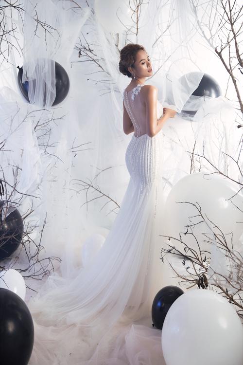 Mặt lưng váy được tạo dựng từ voan mỏng giúp phô diễn nét đẹp nơi tấm lưng thon, làn da mịn màng của tân nương. Hàng cúc được làm từ ngọc trai tạo sự tinh tế, khiến tấm lưng như được diện trang sức để tôn vẻ yêu kiều của người diện.