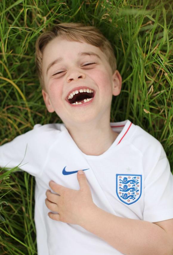 Hoàng tử George mặc áo của đội tuyển Anh nằm trên bãi cỏ trong Điện Kensington. Ảnh: Kensington Palace.