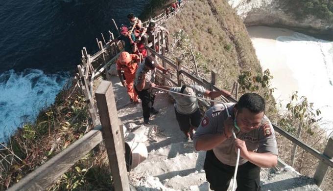 Các sĩ quan Indonesia đưa xác du khách Việt từ bãi biển qua khu vực dốc đá chiều 21/7. Ảnh: NusaBali.com.