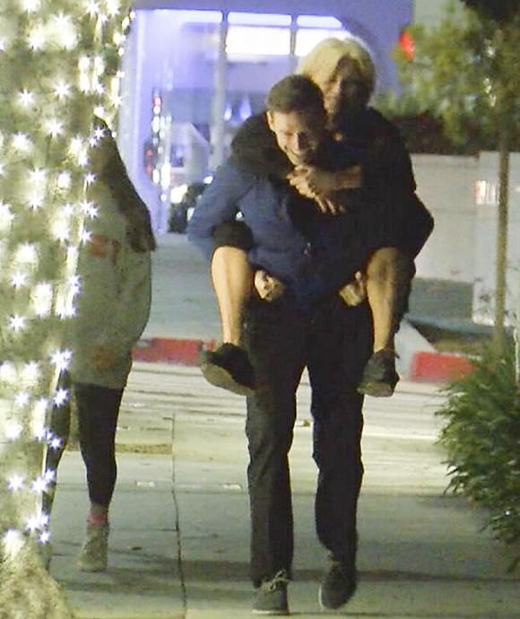 Hugh Jackman cười rạng rỡ khi cõng vợ trên phố.
