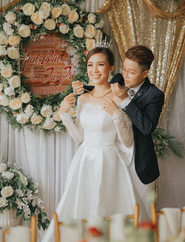 Tú Tri được ông xã âu yếm đeo trang sức cưới. Trông cô rất xinh đẹp trong bộ soiree hở vai.