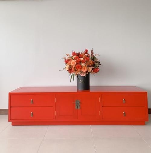 Người đẹp tạo điểm nhấn trong không gian sống tông trắng bằng chiếc tủ màu đỏ cam nổi bật.