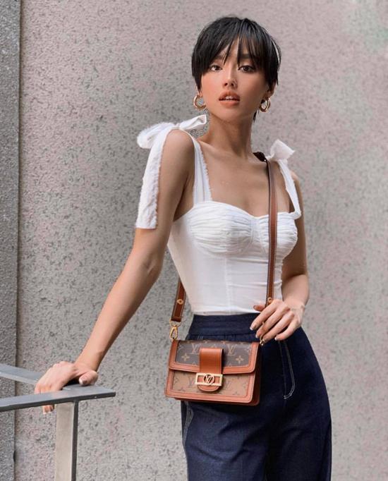 Áo hai dây dáng corset của Khánh Linh trở nên điệu đà hơn nhờ chi tiết thắt nơ điệu đầ. Cô chọn mẫu áo siết eo để phối cùng quần suông dáng rộng và túi Louis Vuitton.