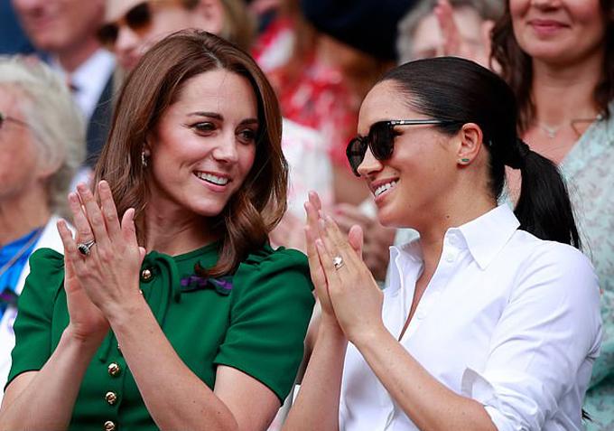 Nữ công tước xứ Cambridge và Nữ công tước xứ Sussex trò chuyện thân mật khi đến xem trận chung kết đơn nữ Wimbledon hôm 13/7. Ảnh: Rex.