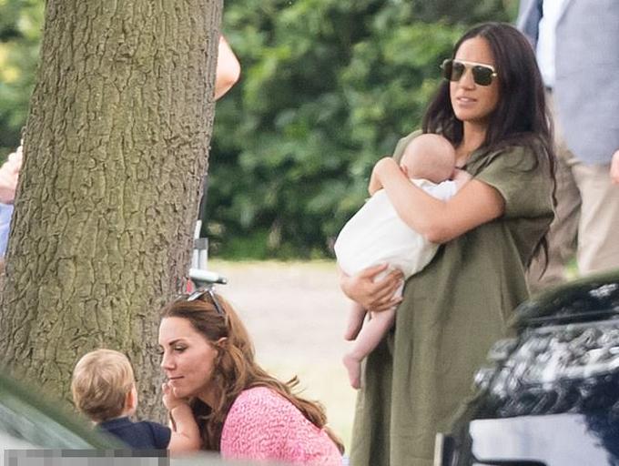 Meghan bế Archie đứng cạnh chị dâu Kate và cháu họ Louis bên lề sân cỏ khi theo dõi trận polo đối đầu giữa Hoàng tử Harry và Hoàng tử William ở hạt Berkshire hôm 10/7. Ảnh: WireImage.
