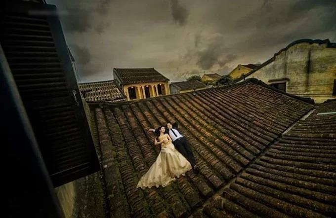 Bức ảnh củ một cặp chụp ảnh trên nóc nhà cổ Hội An.