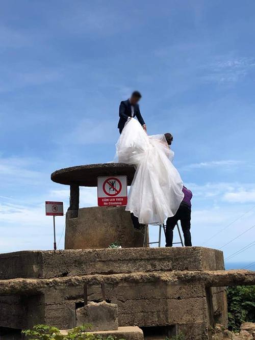 Biển cấm được dựng bên cạnh di tích. Tuy nhiên, ekip chụp ảnh còn mng theo thng để giúp cô dâu, chú rể leo lên di tích.