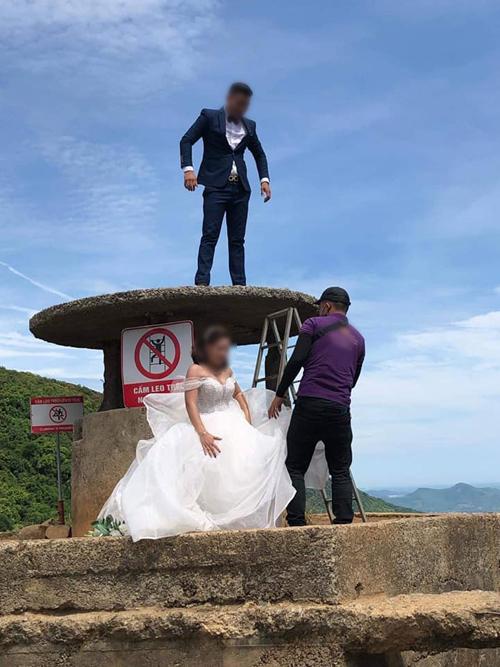 Chú rể trong bộ suit đen đã leo lên Hải Vân Qun, nh cùng một người củ ekip chụp ảnh cưới tiếp tục hỗ trợ cô dâu leo lên di tích để có tấm hình đẹp.