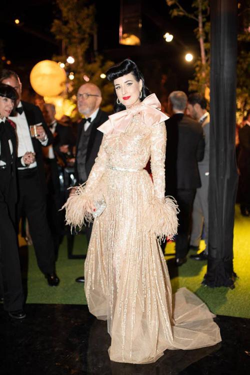 Nữ vũ công thoát y Dit VonTeese diện bộ đầm ánh kim có điểm nhấn là nơ to bản và cổ áo tu ru.