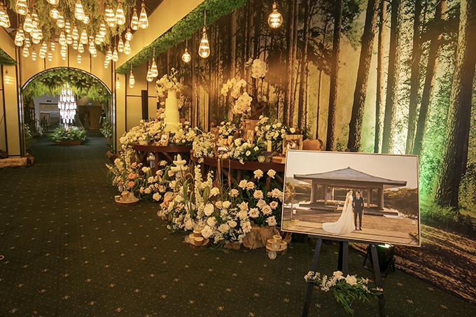 Khu vực bàn gllery được tô điểm với ho tươi và ảnh cưới củ hi vợ chồng.