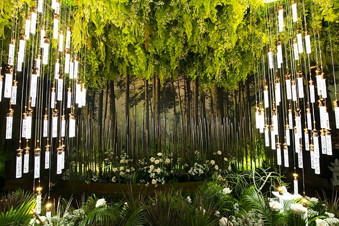 Phông nền ở khắp nơi trong không gin cưới đều là hình ảnh một khu rừng. Cả hi còn sử dụng đèn phát sáng thy cho nến, tạo sự lung linh cho không gin.