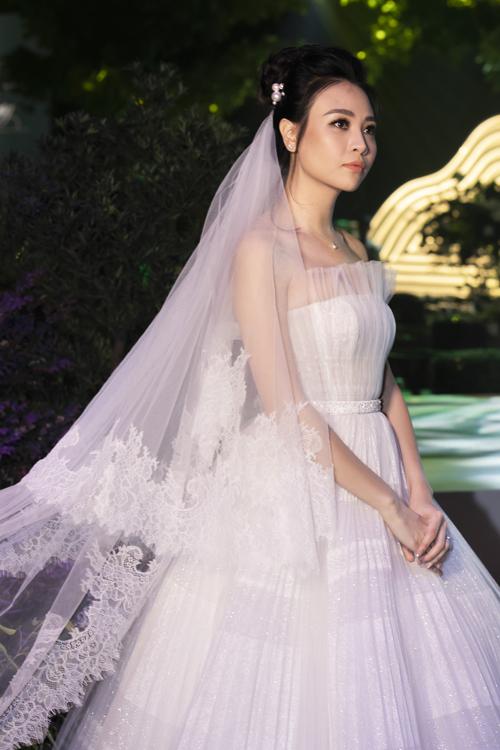 Mẫu đầm quây được nhấn nhá lớp vải lưới dập lytạo nếp gấp,làm tăng thêm phần nền nã, dịu dàng của cô dâu. Tùng váy được thiết kế, xử lý gọng tỉ mỉ giúp bộ cánh có đượcsự bồng bềnh.