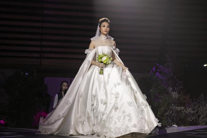 Bộ cánh mà cô dâu diện để thực hiện nghi lễ cưới là sáng tạo của NTK Trần Hùng. Đây cũng là mẫu đầm cưới đầu tiên mà Trần Hùng thiết kế.