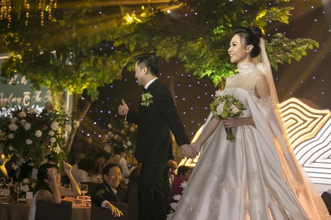 Váy có thiết kế cổ illusion với phần voan mỏng kết nối hai loại cổ áo. Đàm Thu Trang chuộng các thiết kế váy có tay dài, giúp từng cái nhấc tay trở nên nữ tính hơn.