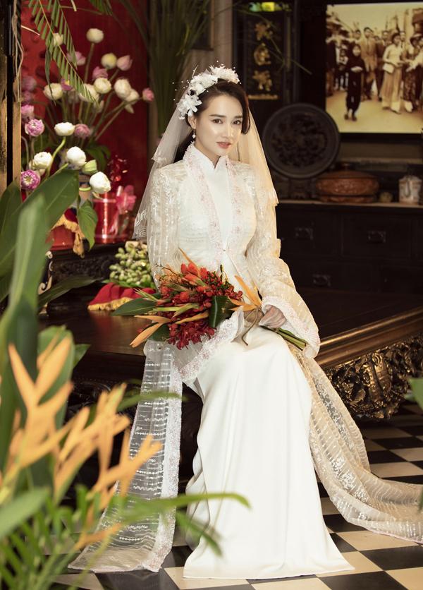 Áo dài trắng với voan trùm đầu kiểu cổ điển cũng được nhiều người ưa chuộng. Để cô dâuthêm phần thướt tha, nổi bật nhà thiết kế cho Nhã Phương khoác ngoài mộtchoàng mỏng.