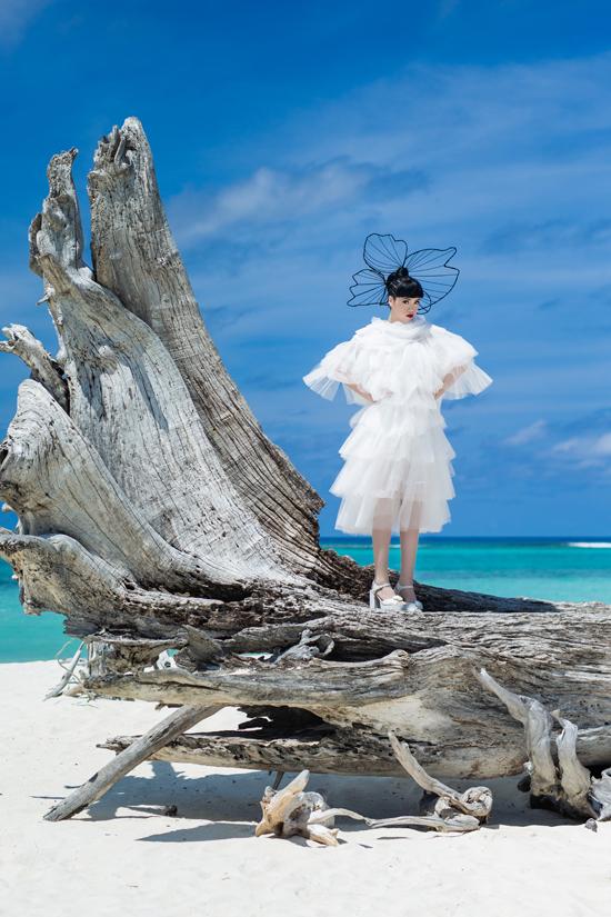 Jessica Minh Anh chọn thêm kiểu hoa đội đầu kiểu dáng độc đáo để mix cùng váy xếp tầng khi chụp ảnh trên bờ biển nổi tiếng châu Á.