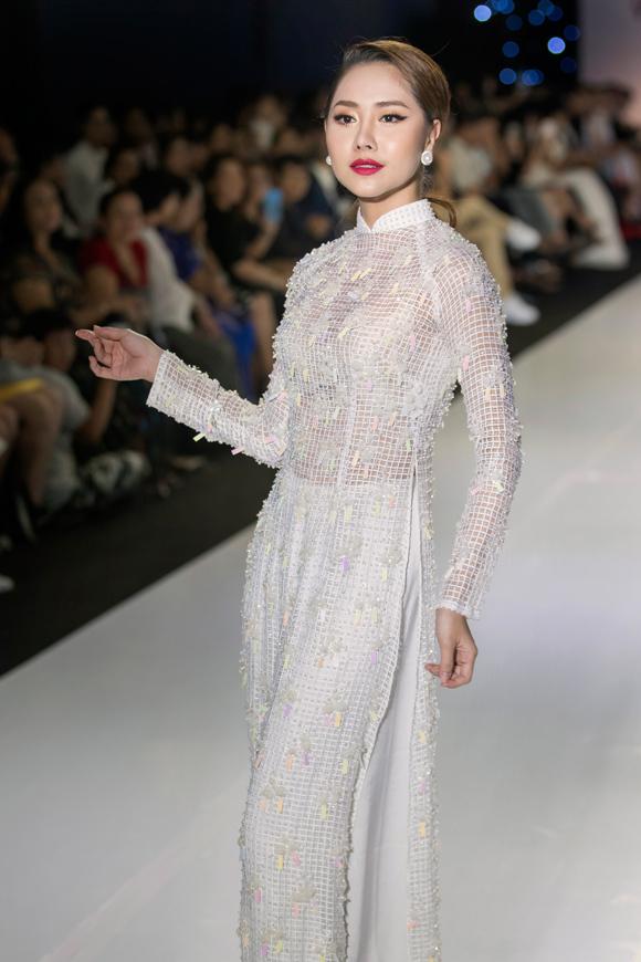 Áo dài của diễn viên Cô Thắm về làng Tường Vi thêm nổi bật nhờ được điểm xuyết vật liệu bắt sáng.