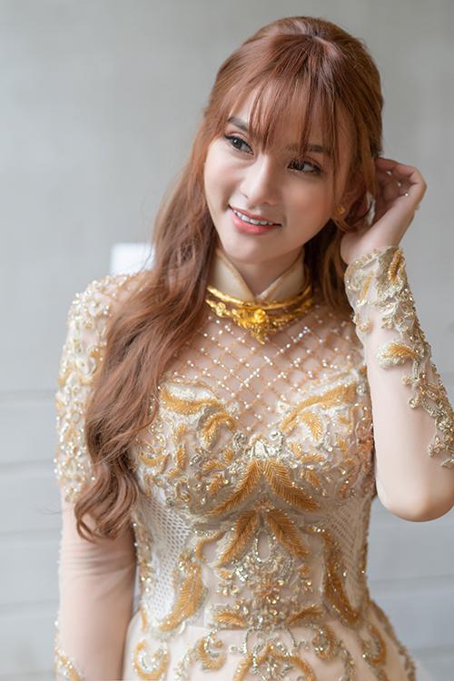 Mẫu áo dài nữ được NTK thực hiện với phom dáng cách điệu từ váy cưới, làm từ 3 lớp vải voan tạo độ chuyển màu nhẹ nhàng, được đính kết ren thủ công. Cổ trụ thấp kết hợp cổ cúp ngực tạo nên nét tươi trẻ, thanh khiết cho cô dâu.