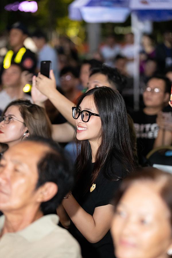 Cô không make-up, mặc áo tối màu và đeo kính để tiện quan sát các thí sinh.