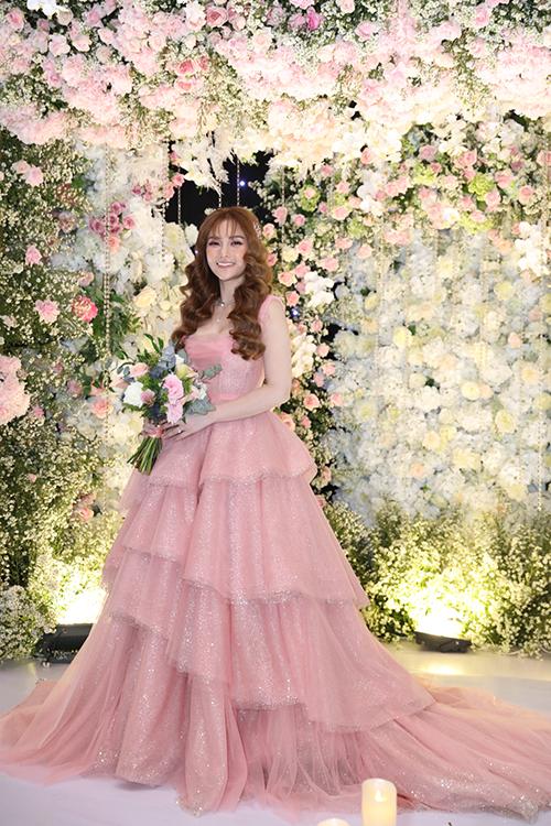 Thu Thủy muốn diện váy hồng để đón khách, phù hợp với sở thích về màu sắc cũng như cá tính nhẹ nhàng của cô. Cô dâu lựa chọn kiểu trang điểm tông hồng và tóc xoăn sóng nước cho dịp hỷ sự.