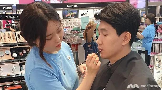 Một chàng trai Hàn Quốc thử sản phẩm chăm sóc môi tại cửa hàng mỹ phẩm. Ảnh: Lim Yun Suk.