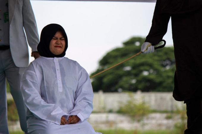 Cô gái Indonesia nhăn nhó vì đau khi bị quất 100 roi công khai hôm 31/7. Ảnh: The Mega Agency.