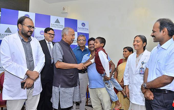 Bố của Ravindranath bế con trai cảm ơn các bác sĩ ở bệnh viện Nha khoa Saveetha, thành phố Chennai sau ca phẫu thuật nhổ răng thành công. Ảnh: Caters News Agency.