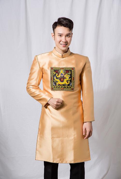 Áo dài mang sắc vàng trang trọng, nam tính, có điểm nhấn là khối họa tiết cung đình. Áo có độ dày, tạo cảm giác chững, giúp định hình phom dáng dễ dàng.