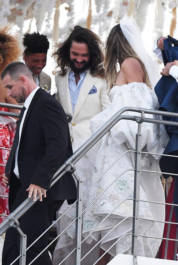 Chú rể Tom Kaulitz mặc vest trắng kết hợp với sơ mi xanh.