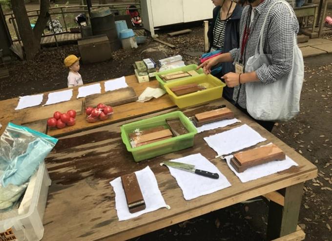 Những chiếc bàn gỗ được đặt giữa công viên cùng các đồ dùng nhà bếp để trẻ nhỏ thực hành với cha mẹ.